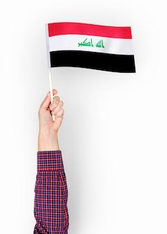 Persona que agita la bandera de la república de iraq