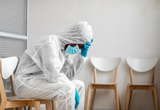 Persona que está cansada después de desinfectar un área peligrosa