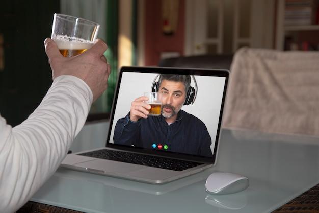 Persona que comparte un vaso de cerveza con su amigo a través de una computadora portátil durante el aislamiento de cuarentena