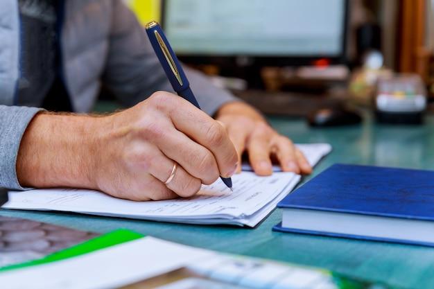Persona que completa la mano del hombre con la pluma y el negocio del formulario de solicitud