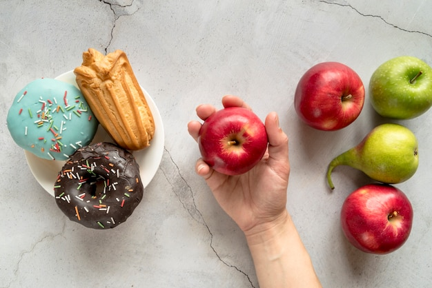 Persona que elige frutas sobre comida de confitería contra fondo concreto