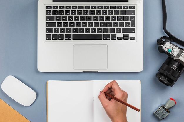 Persona que escribe en el cuaderno en la mesa con el portátil