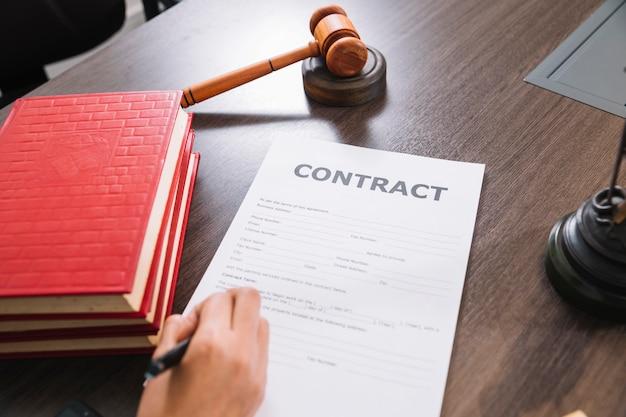 Persona que escribe en el documento en la mesa con libros y martillo