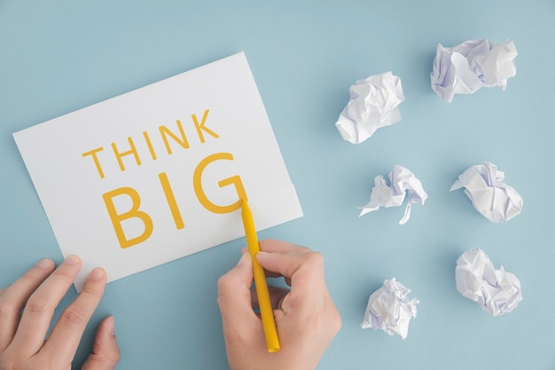 Una persona que escribe piensa en grande sobre papel con crayón amarillo sobre fondo azul
