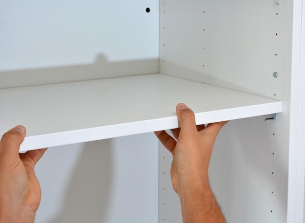 Persona que hace un armario de madera blanco con tornillos.