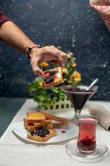 Una persona que hace un brindis con mermelada. un vaso de té negro alrededor.