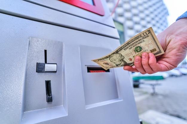 Persona que inserta un billete de dólar en la terminal de autoservicio para el pago