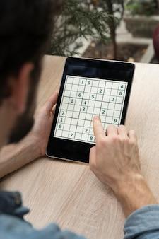 Persona que juega un juego de sudoku en una tableta