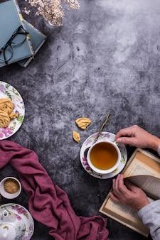 Una persona que lee un libro mientras toma un té sobre una mesa con algunas galletas y una tela morada