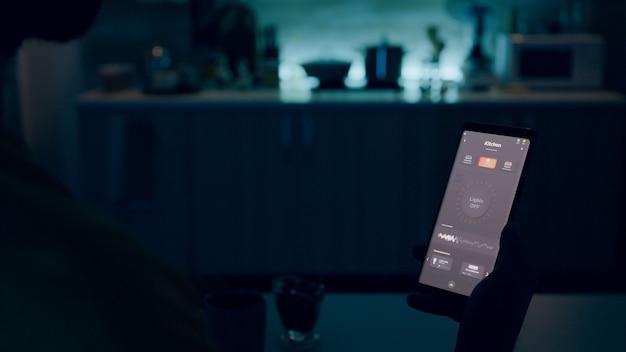 Persona que mira el teléfono inteligente con la aplicación de luces inteligentes para el hogar sentado en la cocina de la casa con sistema de iluminación de automatización, encendiendo bombillas con comando de voz