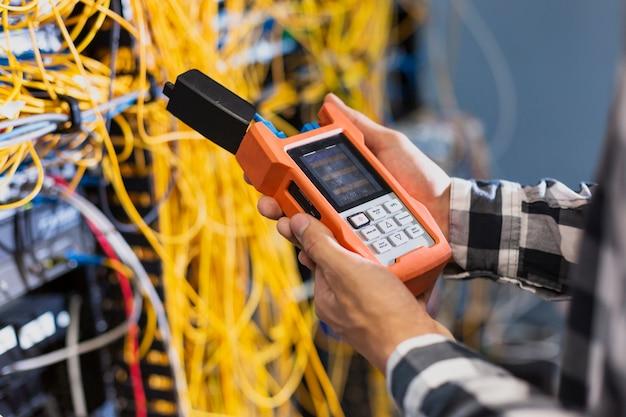 Persona que muestra el probador de fibra óptica