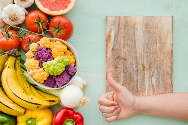 Una persona que muestra signo de thumbsup sobre la tabla de cortar y comida sana fresca