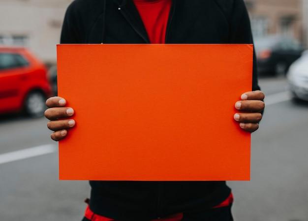 Persona que muestra un tablero en blanco para apoyar un movimiento.