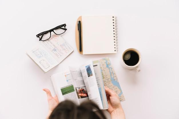 Una persona que pasa las páginas de la guía turística con pasaporte; los anteojos; bloc de notas espiral y taza de café sobre fondo blanco