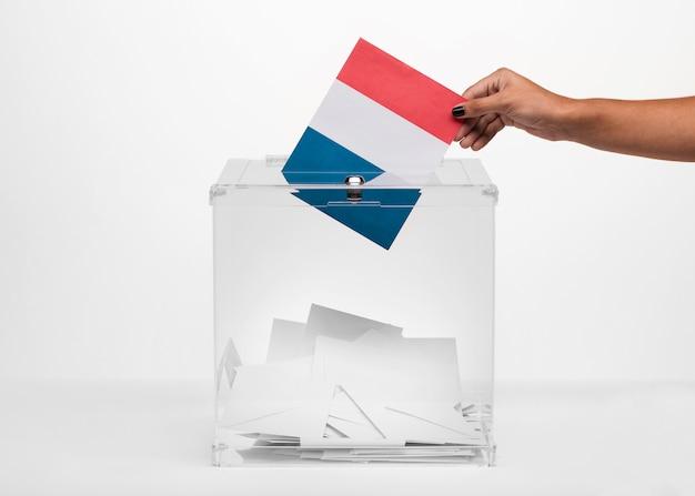 Persona que pone la tarjeta de la bandera de francia en la urna