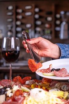 Persona que pone una variedad de surtido de carnes en el plato detrás de una copa de vino
