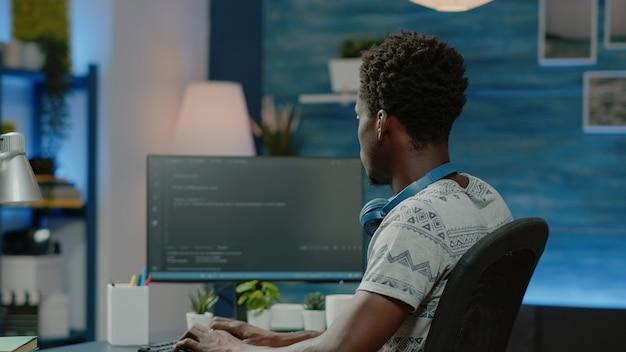 Persona que programa el firewall del sitio web con códigos en la computadora