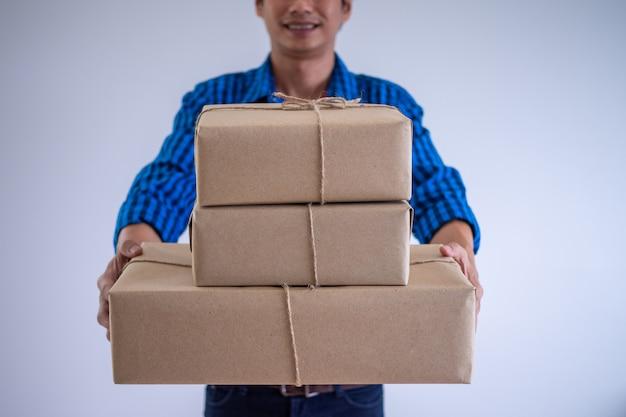 La persona que realiza la entrega tiene el paquete que se entregará al cliente en línea.