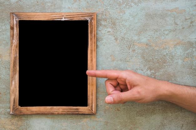 Una persona que señala el dedo en el marco en blanco de madera sobre el fondo del grunge