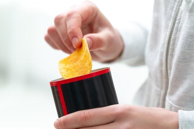 Persona que sostiene la caja de patatas fritas con patatas fritas saladas crujientes picante en las manos. comida chatarra y alimentación poco saludable