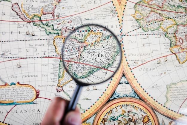 Persona que sostiene la lupa sobre el mapa que muestra las ciudades peruanas