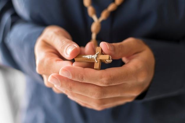 Persona que sostiene el rosario con cruz