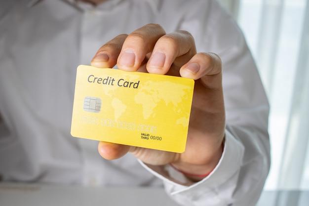 Persona que tiene una tarjeta de crédito amarilla