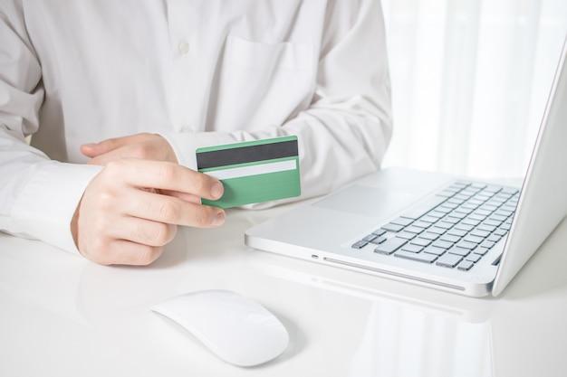 Persona que tiene una tarjeta de crédito verde con una computadora portátil y un mouse de computadora sobre una mesa blanca