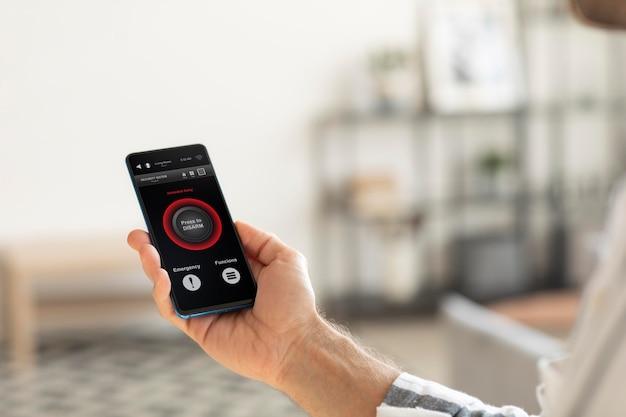 Persona que tiene un teléfono inteligente con una aplicación de automatización del hogar