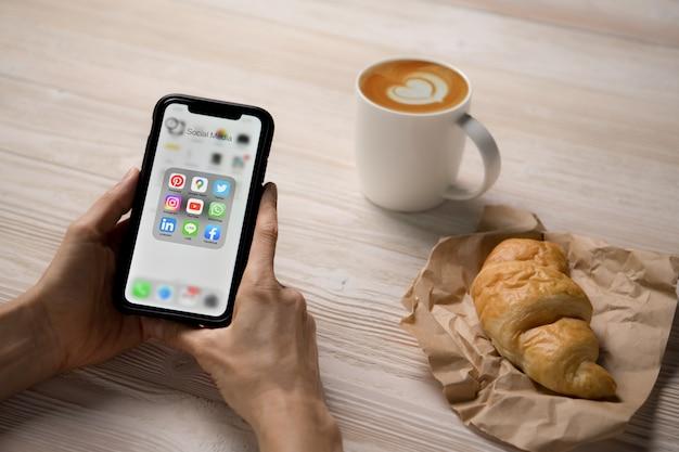 Persona que tiene un teléfono inteligente con iconos de redes sociales en la pantalla de la cafetería.