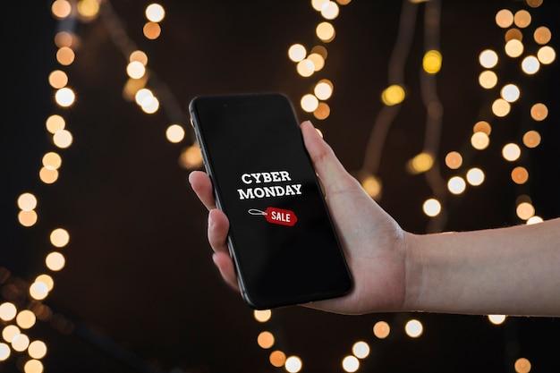 Persona que tiene teléfono inteligente con inscripción cyber monday.
