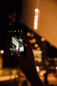 Persona que toma la foto de la arquitectura moderna en la ciudad de noche en el teléfono móvil