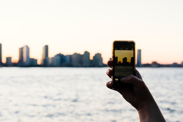Persona que toma la foto de la puesta de sol de la ciudad en el teléfono inteligente