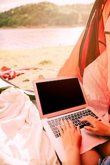 Persona que trabaja en la computadora portátil al aire libre