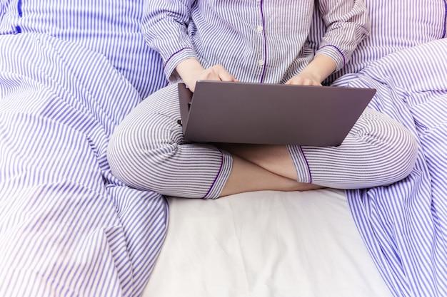 Persona que trabaja en la computadora portátil en la cama mientras está vestida en pijama