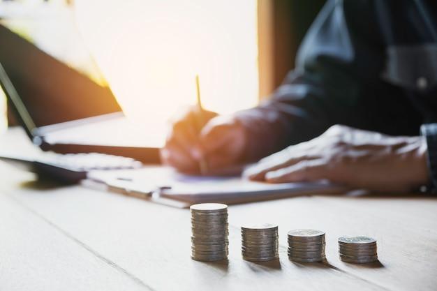 Persona que trabaja y escribe en el cuaderno con la pila de monedas para el concepto financiero y de contabilidad.