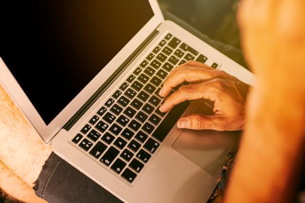 Persona que trabaja de forma remota en una computadora portátil compacta