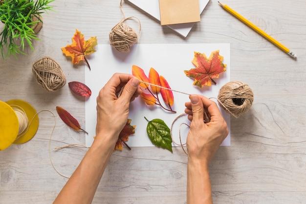 Una persona que usa una cuerda con hojas de otoño falsas sobre fondo de madera