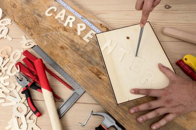 Persona que usa herramientas para crear vista superior de palabra de carpintería