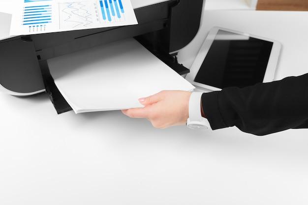 Persona que usa la impresora para escanear e imprimir documentos