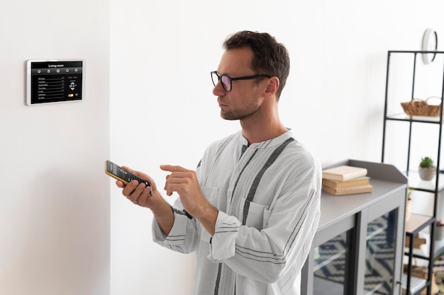 Persona que usa un teléfono inteligente en su hogar automatizado