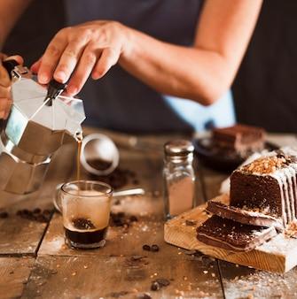 Una persona que vierte el café espresso en vaso con rebanadas de pastel en una tabla de cortar