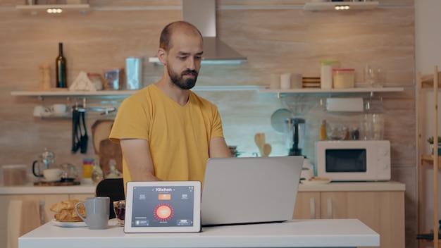 Persona remota que trabaja en una casa moderna dando un comando de voz a la tableta con la aplicación de hogar inteligente y las luces encendidas