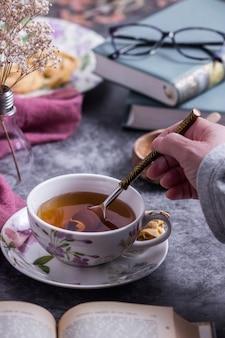 Una persona revolviendo el té con una cuchara