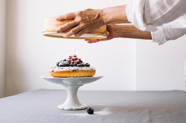Persona rocía pastel con polvo