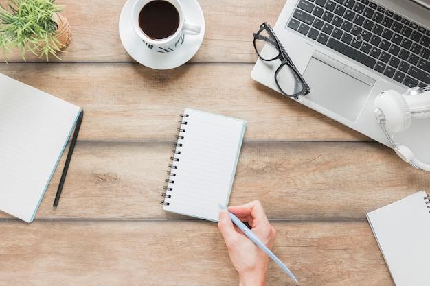 Persona sin rostro escribiendo en cuaderno cerca de papelería y portátil en la mesa