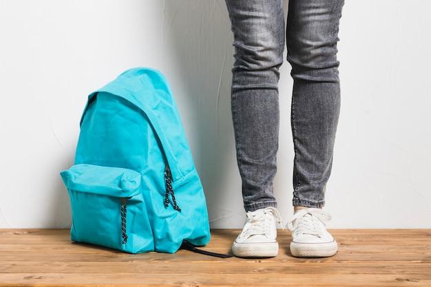 Persona sin rostro de pie junto a la mochila en la mesa de madera