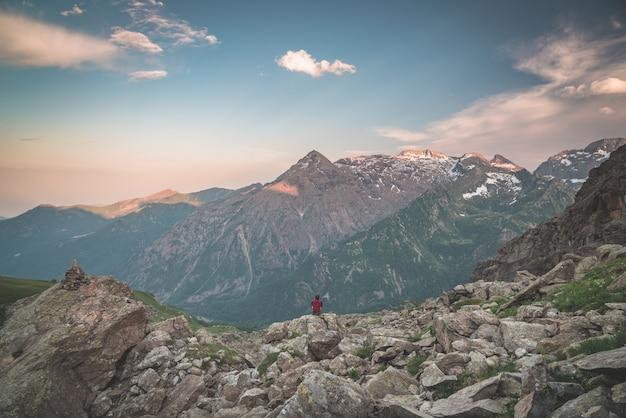 Una persona sentada en un terreno rocoso y viendo amanecer en los alpes