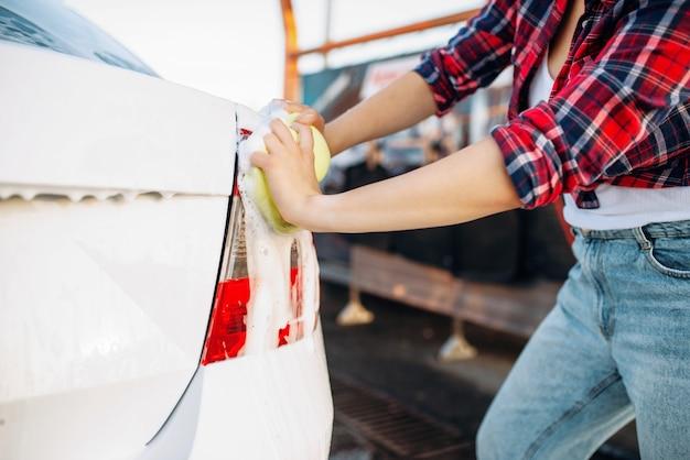 Persona de sexo femenino con esponja para fregar las luces traseras del vehículo con espuma, lavado de autos. mujer joven en lavado de automóviles de autoservicio. lavado de autos al aire libre en verano
