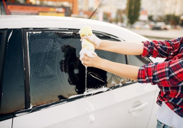 Persona de sexo femenino con esponja para fregar la ventana del vehículo con espuma, lavado de autos. mujer joven en lavado de automóviles de autoservicio. lavado de autos al aire libre en verano